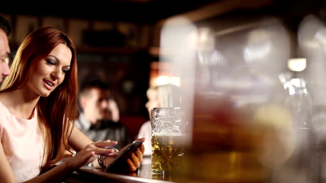 Man and woman in the Pub using tablet II video
