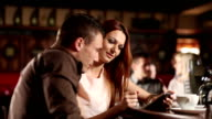 Man and woman in the Pub using tablet video