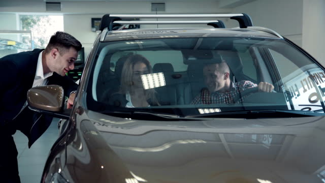 Man and woman inside new automobile video