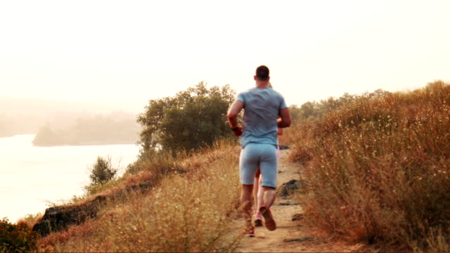 Man and woman jogging along a mountain path back view video