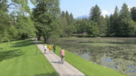 AERIAL Man and woman jogging through park along a lake video
