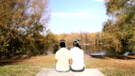 Man and woman listening to music using headphones while sitting by lake video