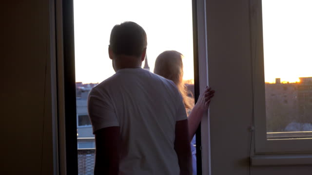 Man and woman looking at the city from balcony video