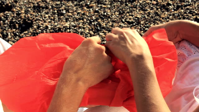 Man and Woman Open A Red Bundle on the Beach video