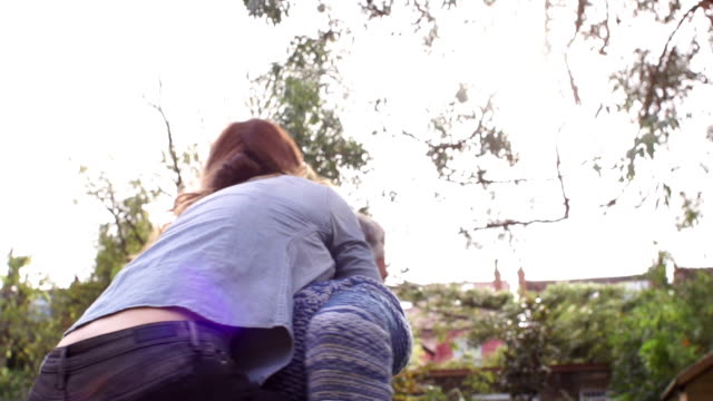 Man and woman Piggy Back, lens flare,  Super Slow motion video