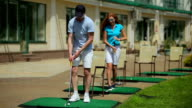 Man and woman playing golf near a clubhouse video