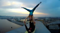 Man and woman practicing acrobatic yoga on top of bridge, dangerous sports video