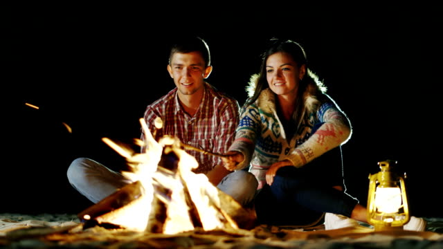 Man and woman relaxing evening around the campfire, roast marshmallows on sticks fire. Nearby is a kerosene lamp video