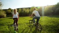 Man and woman riding bicycles on the green meadow. video