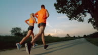 SLO MO TS Man and woman running at sunset video