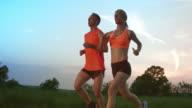 SLO MO TS Man and woman running at sunset video