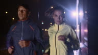 SLO MO man and woman running in the city at night video