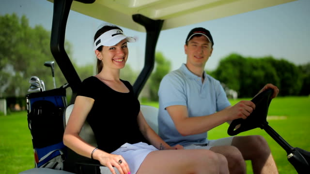 Man and woman siiting in the cart at golf field video