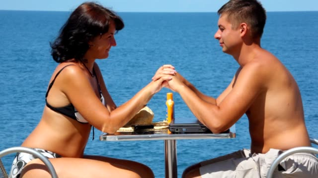 Man and woman sits at table with join hands kissing video