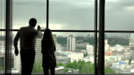 Man and woman stand near a window. video