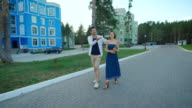 Man and woman strolling along the fashionable residential area video