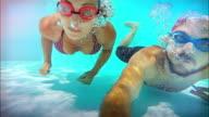 Man and woman swim underwater slowmotion video