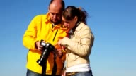 Man and woman takes photocamera in hands, look an it video