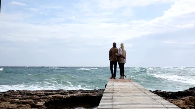 Man and woman walk along boardwalk above sea video