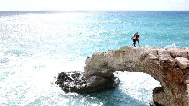 Man and woman walk along crest of natural rock bridge video