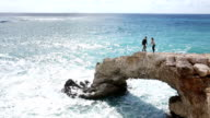 Man and woman walk along crest of natural rock bridge video