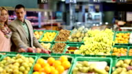 Man And Woman With Trolley By Fruit Counter In Supermarket video