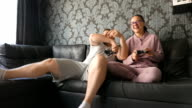 Man and woman young couple are playing video games and having fun on the couch video