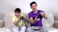 Man and young boy with video game controllers smiling video