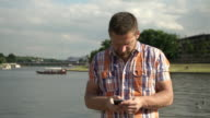 Man answering smartphone by the river video