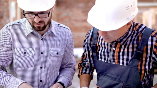 Man Architect and a young foreman are reviewing the blueprints of the building that will be applied for the construction video
