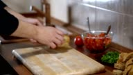 A man arranges bread for cooking bruschetta video