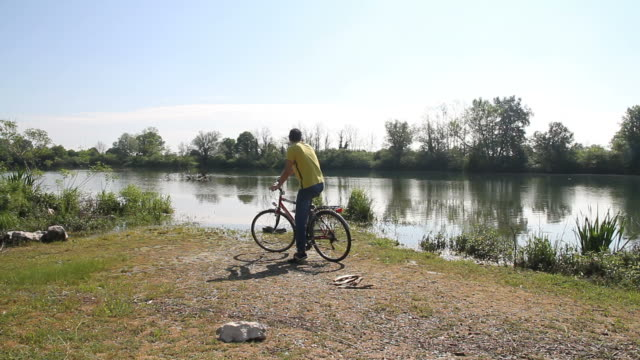 Man arrive at river with bicycle video