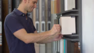 Man at a floor store looking at samples video