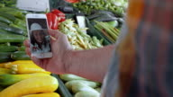 Man at a marketplace on videocall with his wife video