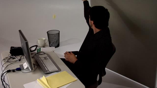 Man at desk throwing paper in garbage video
