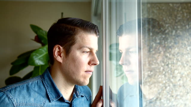 Man at home looking outside and smile into camera video