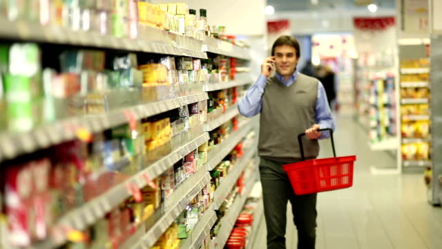 Man at supermarket with cellphone video
