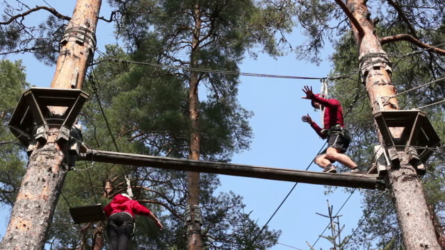 Man balancing on High Ropes course beam video