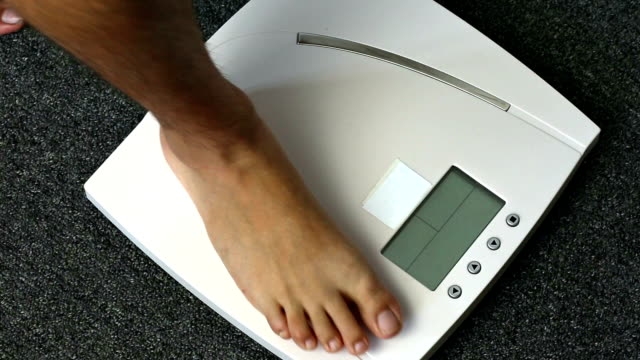 Man barefoot legs stepping on digital floor scales video