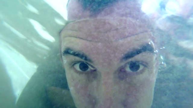 man bathes in bathroom dives underwater happy video
