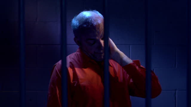 Man behind bars sitting in his cell video