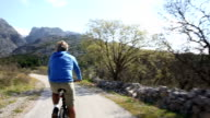 Man bikes along rural road towards mountains, POV view video