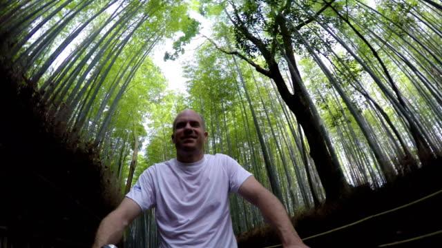Man biking through a bamboo forest video