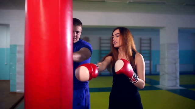 man boxer coach teaches girl boxing at the gym video