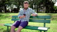 Man browsing smartphone on bench in park, steadicam. video
