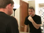 Man brushes teeth in front of mirror video