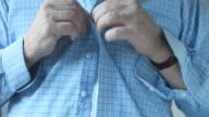 man buttons shirt video