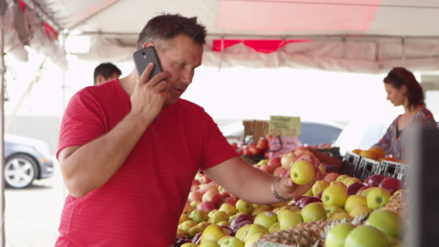 Man buying fresh fruits while on the cellphone video