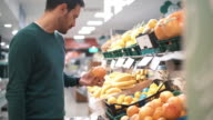 Man buying fruit in supermarket. video