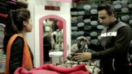 Man buying garments for family and confident saleswoman helping him. video